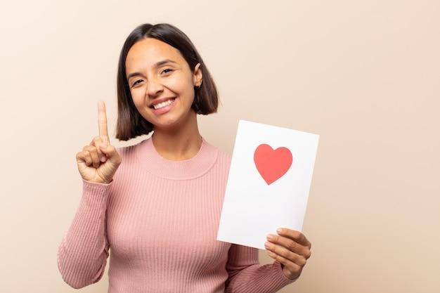 Młoda latynoska uśmiechnięta i wyglądająca przyjaźnie, pokazująca numer jeden lub pierwsza z ręką do przodu, odliczająca