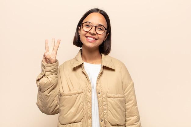Młoda latynoska uśmiechnięta i wyglądająca przyjaźnie, pokazująca numer trzy lub trzeci z ręką do przodu, odliczający