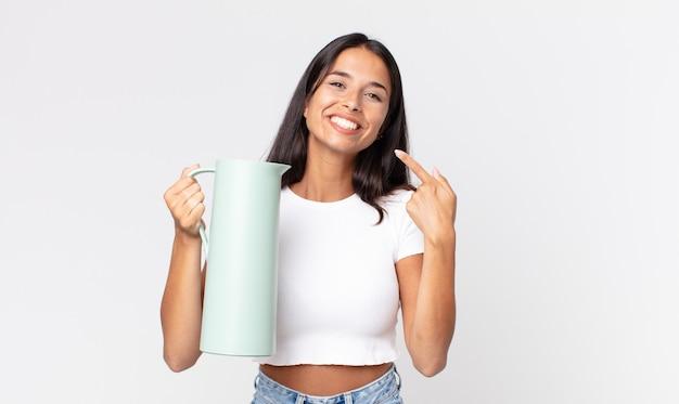 Młoda latynoska uśmiechnięta pewnie, wskazująca na swój szeroki uśmiech i trzymająca termos z kawą