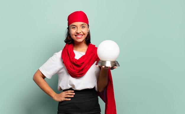 Młoda latynoska uśmiechnięta radośnie z ręką na biodrze i pewną siebie, pozytywną, dumną i przyjazną postawą
