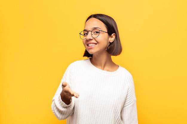 Młoda latynoska uśmiechnięta, wyglądająca na szczęśliwą, pewną siebie i przyjazną, oferująca uścisk dłoni w celu zawarcia umowy, współpracująca