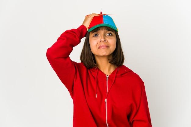 Młoda latynoska w czapce z izolowanym śmigłem jest zszokowana i przypomniała sobie ważne spotkanie