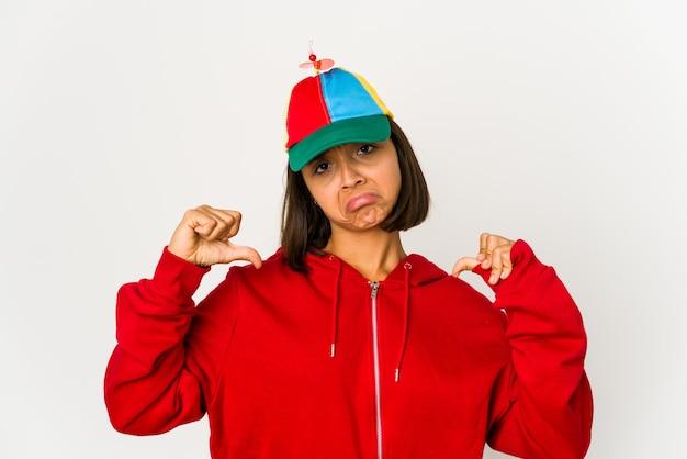 Młoda latynoska w czapce z odizolowanym śmigłem czuje się dumna i pewna siebie, przykład do naśladowania.