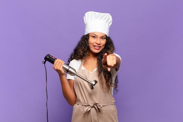 Młoda latynoska wskazująca z zadowolonym, pewnym siebie, przyjaznym uśmiechem, wybierająca ciebie. koncepcja szefa kuchni