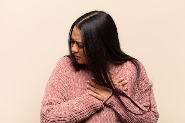 Młoda latynoska wygląda na smutną, zranioną i załamaną, trzymając obie ręce blisko serca, płacząc i czując się przygnębiona