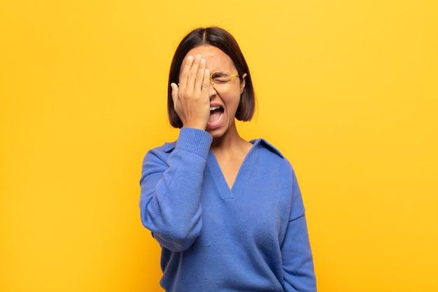 Młoda latynoska wygląda na zaspaną, znudzoną i ziewającą, z bólem głowy i jedną ręką zakrywającą połowę twarzy