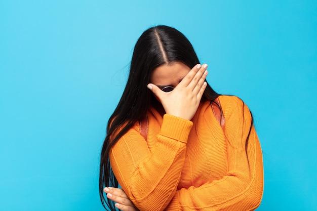 Młoda latynoska wygląda na zestresowaną, zawstydzoną lub zdenerwowaną, z bólem głowy, zakrywa twarz dłonią