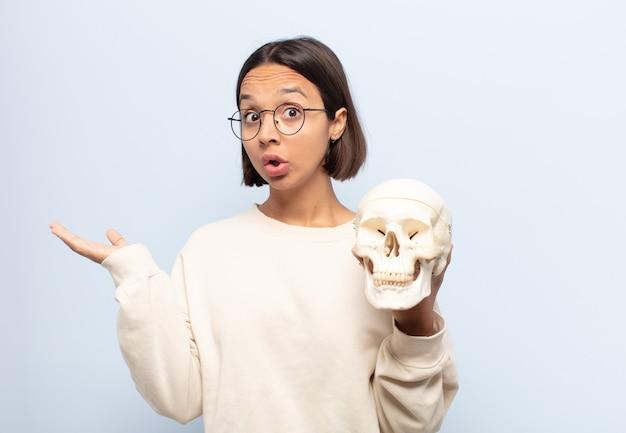 Młoda latynoska wyglądająca na zaskoczoną i zszokowaną, z opuszczoną szczęką, trzymająca przedmiot z otwartą ręką z boku