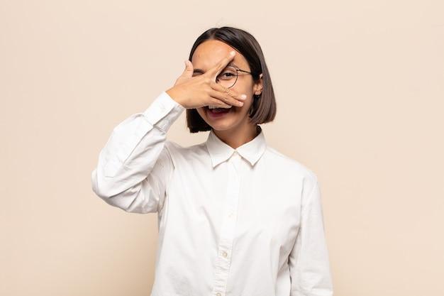 Młoda latynoska wyglądająca na zszokowaną, przestraszoną lub przerażoną, zakrywającą twarz dłonią i zaglądającą między palce