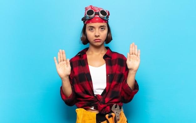 Młoda latynoska wyglądająca poważnie, niezadowolona, zła i niezadowolona, zakazująca wejścia lub mówiąca stop z otwartymi dłońmi
