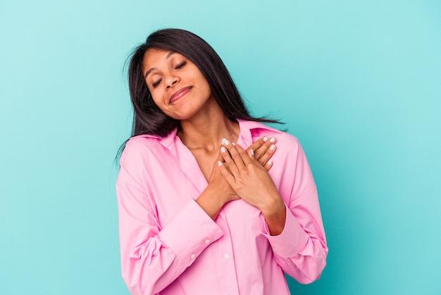 Młoda latynoska wyizolowana na niebieskim tle ma przyjazny wyraz, przyciskając dłoń do piersi. koncepcja miłości.