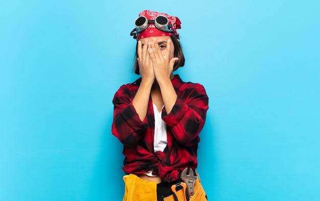 Młoda latynoska zakrywająca twarz rękami, zaglądająca między palce ze zdziwieniem i patrząc w bok