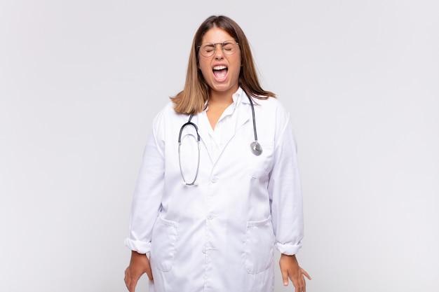Młoda lekarka agresywnie krzyczy, wygląda na bardzo złą, sfrustrowaną, oburzoną lub zirytowaną, krzyczy `` nie ''