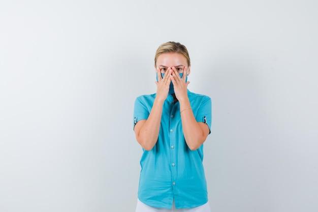 Młoda lekarka patrząca przez palce w mundurze medycznym