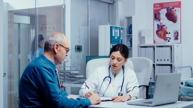 Młoda lekarka pisania nowego przepisu na leki dla starszego pacjenta. opieka zdrowotna w nowoczesnym szpitalu lub przychodni prywatnej, profilaktyka chorób i konsultacje w gabinecie lekarskim leczenie diagnostyka leków exp