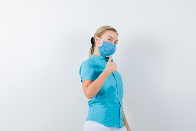Młoda lekarka pokazując kciuk w górę w mundurze medycznym, masce i wyglądam pewnie