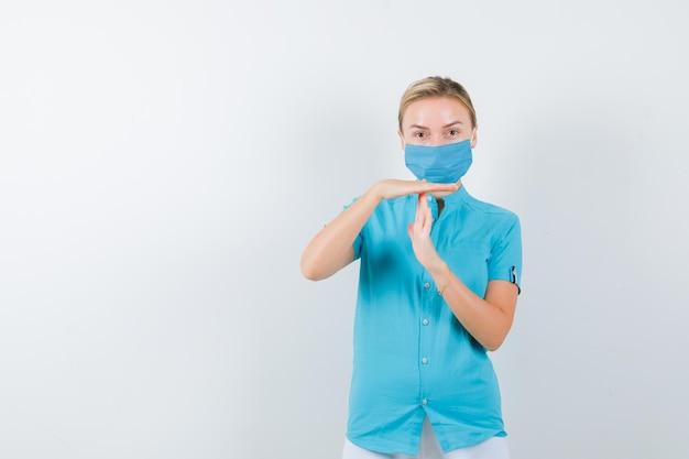 Młoda lekarka pokazująca gest limitu czasu w mundurze medycznym, masce i wyglądającym pewnie