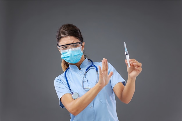 Młoda lekarka trzyma strzykawkę i gestykuluje, jakby była przeciw szczepieniu.
