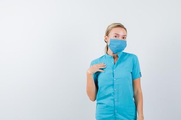 Młoda lekarka trzymająca rękę na klatce piersiowej w mundurze i patrząca niezdecydowana