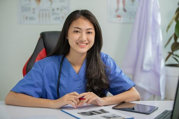 Młoda lekarka uśmiecha się i pracuje w biurze