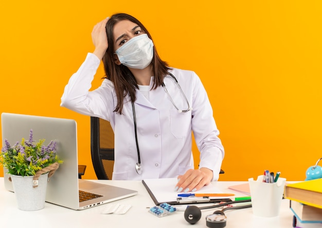 Młoda lekarka w białym fartuchu i masce ochronnej na twarz ze stetoskopem patrząc do przodu zdezorientowana siedzi przy stole z laptopem i dokumentami na pomarańczowej ścianie