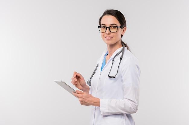 Młoda lekarka w białym fartuchu i okularach za pomocą touchpada podczas komunikowania się z pacjentami online