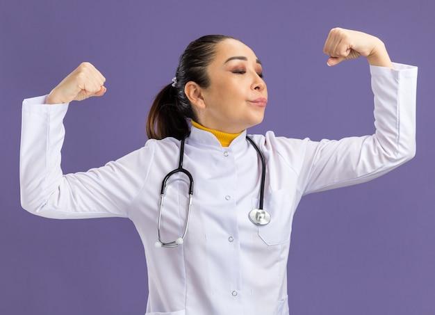 Młoda lekarka w białym fartuchu lekarskim ze stetoskopem wokół szyi unosząca pięści, wyglądająca pewnie, stojąc nad fioletową ścianą