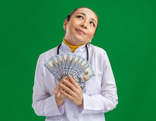 Młoda lekarka w białym fartuchu medycznym ze stetoskopem na szyi patrząca w górę szczęśliwa i zadowolona stojąc nad zieloną ścianą