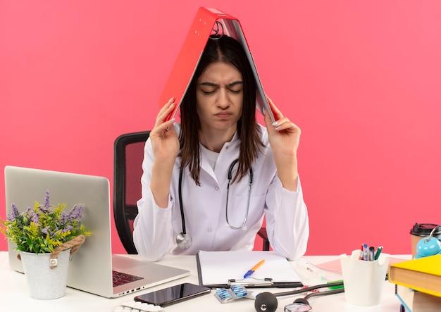 Młoda lekarka w białym fartuchu ze stetoskopem na szyi chowająca folder nad głową wyglądająca na zmęczoną i przepracowaną siedzącą przy stole z laptopem na różowej ścianie