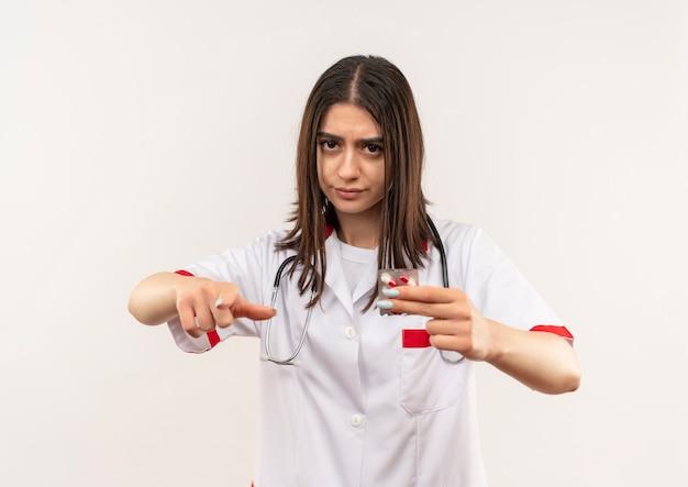 Młoda lekarka w białym fartuchu ze stetoskopem na szyi pokazująca blister z pigułkami wskazującymi palcem wskazującym do przodu z poważną twarzą stojącą na białej ścianie