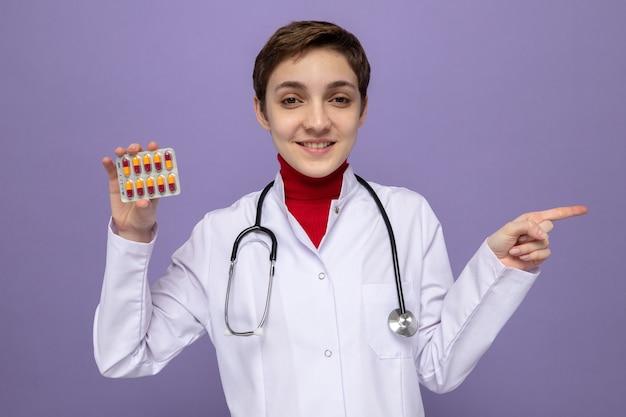 Młoda lekarka w białym fartuchu ze stetoskopem na szyi trzyma blister z tabletkami uśmiechając się radośnie wskazując palcem wskazującym w bok stojąc na fioletowo