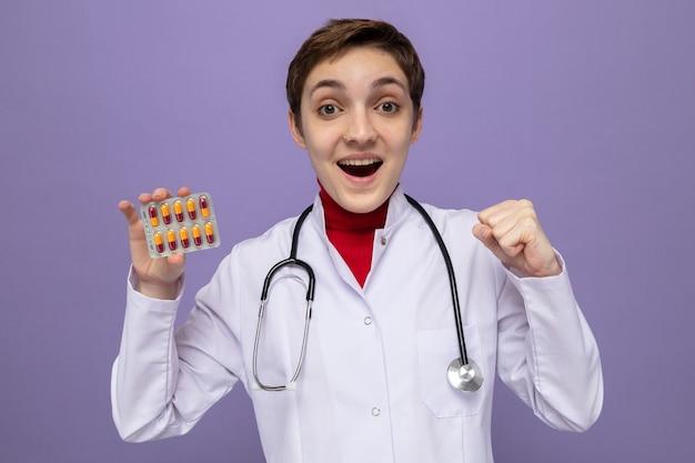 Młoda lekarka w białym fartuchu ze stetoskopem na szyi trzymająca blister z pigułkami szczęśliwa i podekscytowana zaciskająca pięść stojąca nad fioletową ścianą