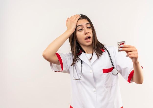 Młoda lekarka w białym fartuchu ze stetoskopem na szyi trzymająca blister z tabletkami patrząc na niego zdezorientowana stojąc nad białą ścianą