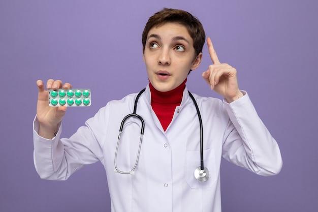 Młoda lekarka w białym fartuchu ze stetoskopem na szyi trzymająca blister z tabletkami patrząca w górę zdziwiona pokazująca palec wskazujący stojący na fioletowo