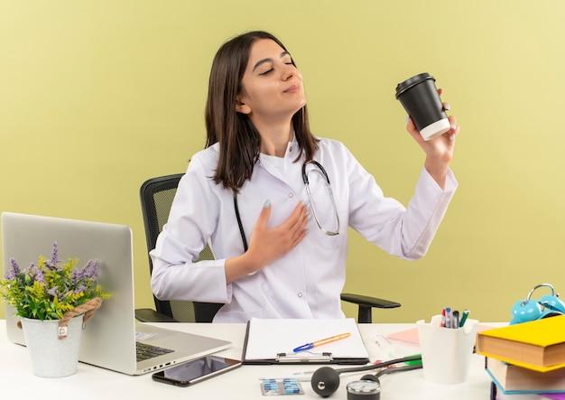 Młoda lekarka w białym fartuchu ze stetoskopem na szyi trzymająca filiżankę kawy czująca pozytywne emocje siedząca przy stole z laptopem nad jasną ścianą