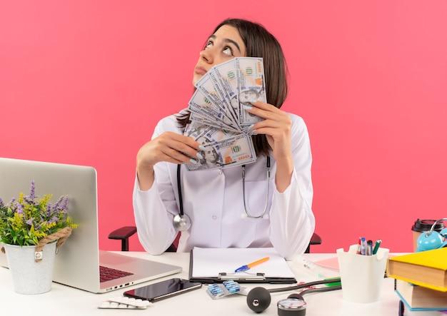 Młoda lekarka w białym fartuchu ze stetoskopem na szyi trzymająca gotówkę patrząc w górę bardzo zadowolona siedzi przy stole z laptopem nad różową ścianą