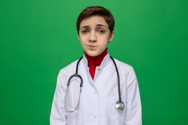 Młoda lekarka w białym fartuchu ze stetoskopem na szyi wygląda na zdezorientowaną i niezadowoloną
