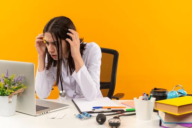 Młoda lekarka w białym fartuchu ze stetoskopem patrząc na ekran swojego laptopa, zdezorientowana i bardzo niespokojna siedzi przy dokumentach na stole nad pomarańczową ścianą