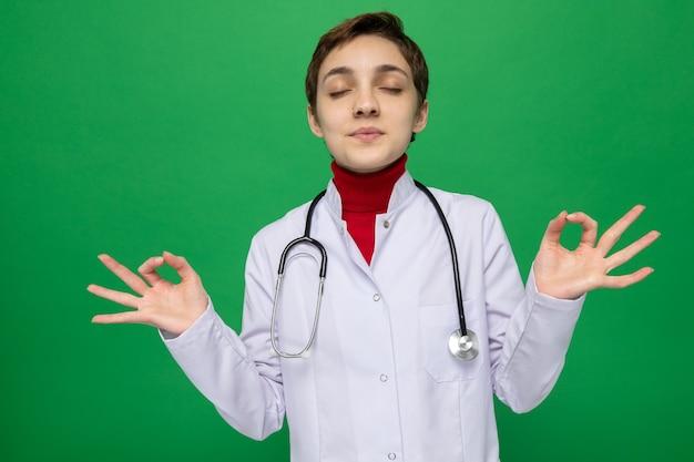 Młoda lekarka w białym fartuchu ze stetoskopem robi gest medytacji, próbując zrelaksować się z zamkniętymi oczami