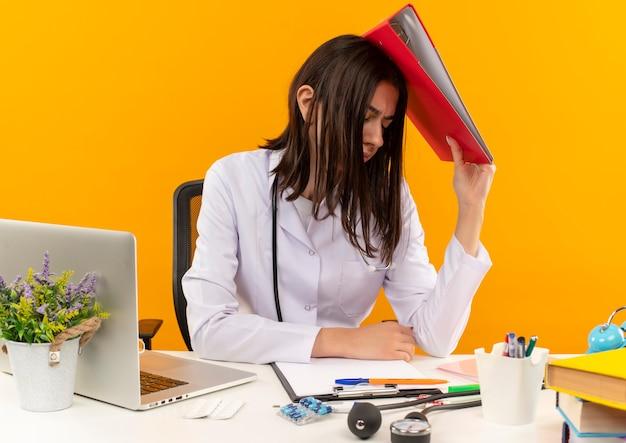 Młoda lekarka w białym fartuchu ze stetoskopem trzymająca folder nad głową, wyglądająca na zmęczoną i przepracowaną, siedząca przy stole z laptopem i dokumentami na pomarańczowej ścianie