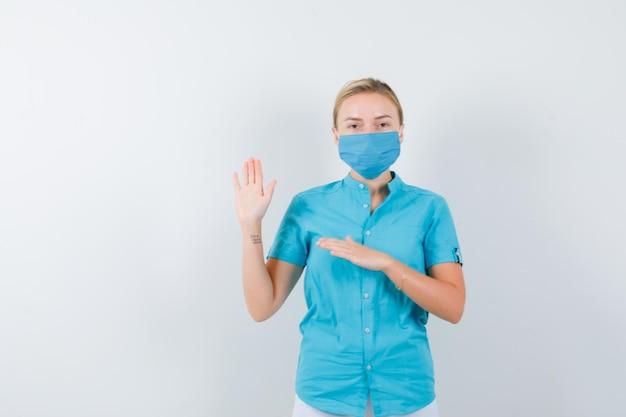 Młoda lekarka w mundurze macha ręką na powitanie i wygląda wesoło