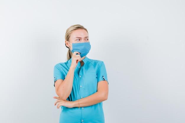 Młoda lekarka w mundurze stojąca w myślącej pozie i patrząca z wahaniem na białym tle