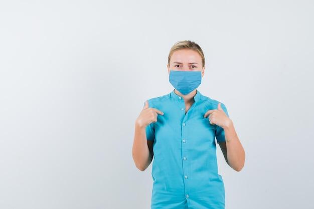 Młoda lekarka w mundurze wskazująca na siebie i patrząca z wahaniem