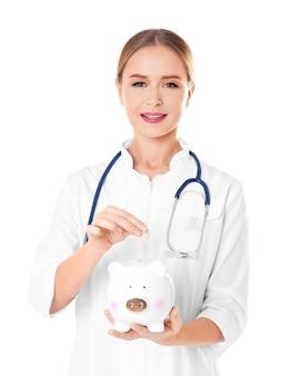 Młoda lekarka wrzucająca monetę do skarbonki na białym