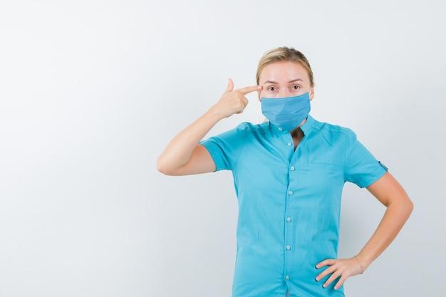 Młoda lekarka wskazując głowę, trzymając rękę na biodrze w mundurze na białym tle
