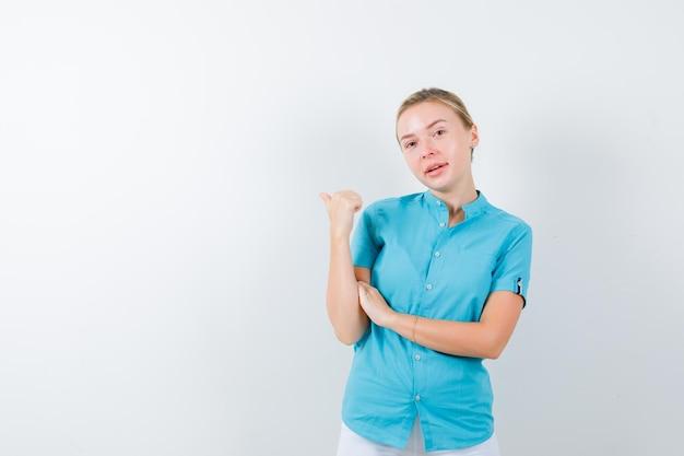 Młoda lekarka wskazująca kciukiem do tyłu w mundurze medycznym, masce i ładnym wyglądzie