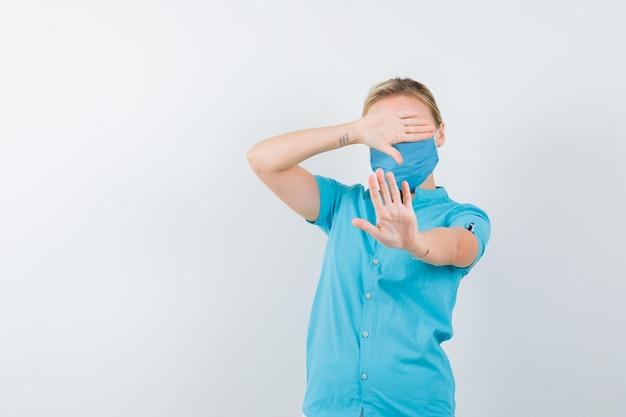 Młoda lekarka zakrywająca oczy rękami, pokazując gest zatrzymania na białym tle