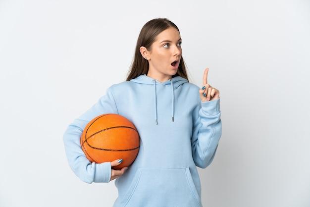 Młoda litewska kobieta gra w koszykówkę na białym tle na białej ścianie myśli pomysł wskazując palcem w górę