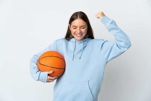 Młoda litewska kobieta gra w koszykówkę na białym tle na białej ścianie robi silny gest