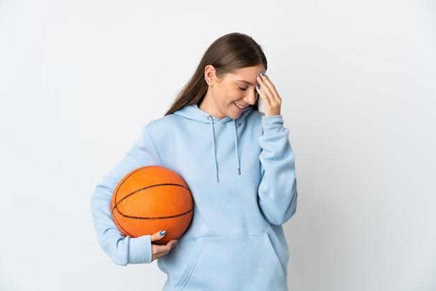 Młoda litewska kobieta gra w koszykówkę na białym tle na białej ścianie, śmiejąc się